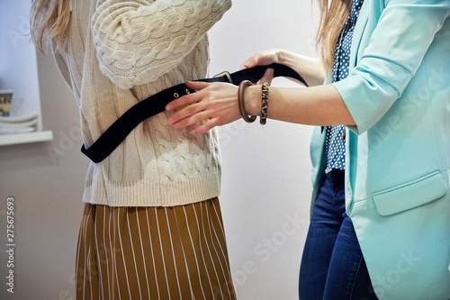 Pinturas sobre lienzo  shop assistant helps lady in beige sweater put on and take off leather belt in s