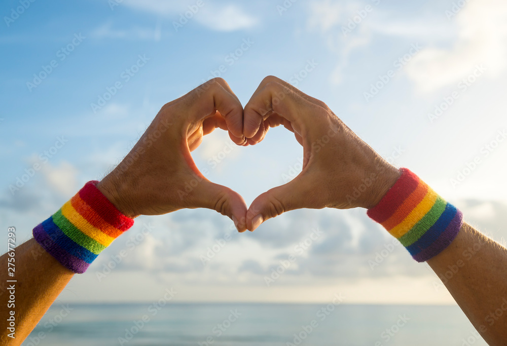 Fototapety, obrazy: Hands wearing LGBTQI pride rainbow colors sport wristbands making a heart gesture above a golden sunset sea horizon