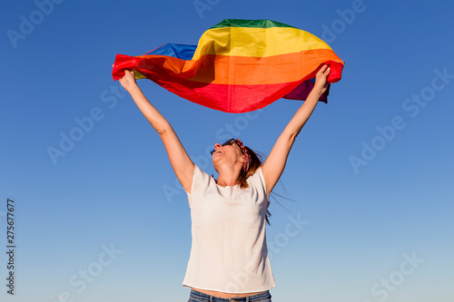 Fotomural  Woman holding the Gay Rainbow Flag over blue sky outdoors