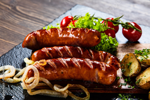 Grilled sausages and vegetables on cutting board Fototapeta