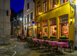 canvas print picture Old street with tables of cafe in Bruges (Brugge), Belgium. Night cityscape of Bruges. Typical architecture of Bruges