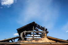 Burnt Roof Of A Wooden House Against The Blue Sky. The Concept Of Home Insurance Against Accidents, Fire In Homes, Safety Rules In Case Of Fire, Restoration Of Property After A Fire. Place For Text.