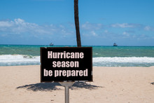Warning Sign On Beach Next To The Trunk Of A Palm Tree On A Sunny Day With A Blue Clear Sky Warning That It Is Hurricane Season And That You Should Be Prepared