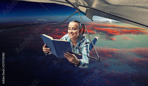 Fotografía  Young woman flying on hang glider. Mixed media