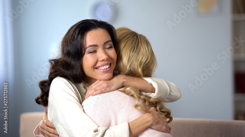 Photo  Two beautiful women hugging and smiling, true old friends meeting, indoors