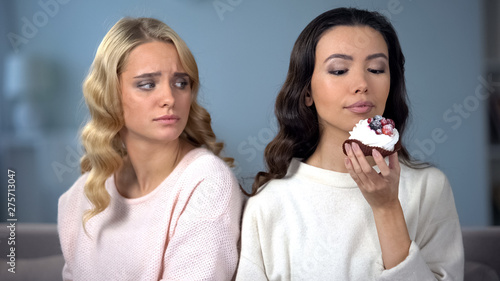 Canvas Print Hungry woman on diet looking at her skinny friend enjoying tasty cake, envy