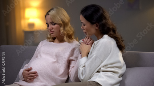 Woman supporting her upset pregnant friend, holding hand, single future mother Wallpaper Mural
