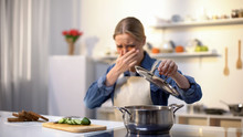 Young Woman Smelling Cooked Soup With Disgusted Face Expression, Spoiled Food