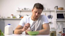 Unhappy Lonely Man Looking With Disgust At Food In Bowl, Lack Of Appetite