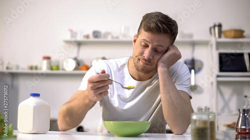 Papel de parede Upset single man eating tasteless cereals for breakfast, lack of appetite