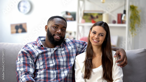 Photo Smiling mixed-race couple sitting on sofa at home and looking at camera, family