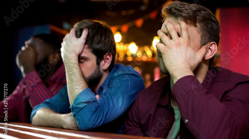 Fotografie, Tablou Multiethnic football fans making facepalm, disappointed with game loss, bar