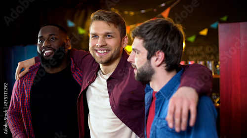 Photo Cheerful multiracial friends hugging, celebrating bachelor party in bar, leisure