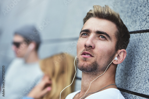 Young attractive Teens listening to music on the same pair of headphones, dressed in stylish clothes against a background of a gray wall. - 275721030