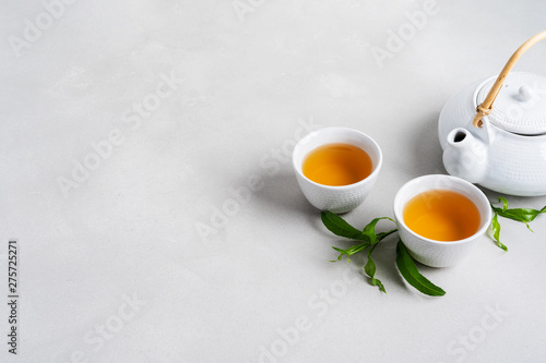 Foto auf Leinwand Tee Tea concept with white tea set of cups and teapot surrounded with fresh tea leaves on concrete background with copy space.