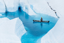 Glacier Kayaking Over Ice Cave And Deep Blue Lake In The Rain.