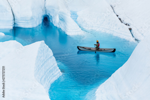 Poster Blanc Glacier kayaking over ice cave and deep blue lake in the rain.