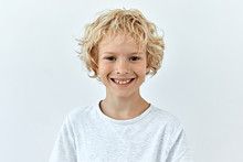 Little Child Boy Portrait Against White Background. Laughter And Joy Emotions
