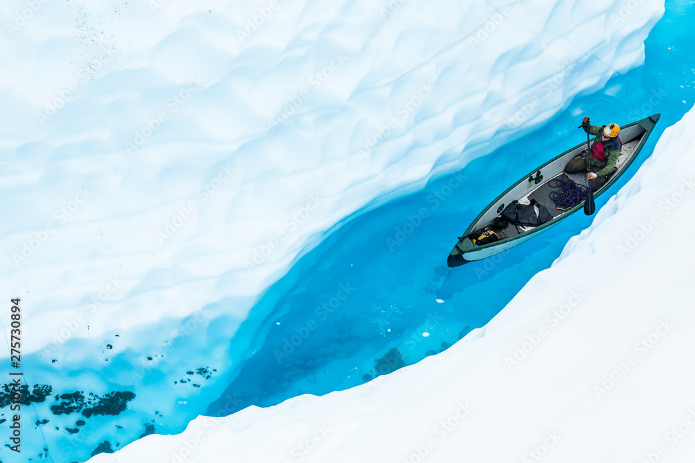 Fototapety, obrazy: Ice climber canoeing in narrow ice canyon from above.