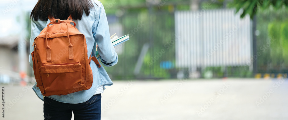 Fototapety, obrazy: Back of student girl holding books and carry school bag while walking in school campus background, copy space banner, education, back to school concept