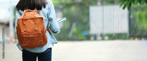 Photo Back of student girl holding books and carry school bag while walking in school