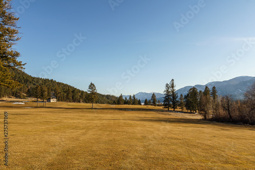 Foto auf Gartenposter Wald FAIRMONT HOT SPRINGS, CANADA - MARCH 22, 2019: Golf Course field in small town in rocky mountains sunny afternoon.