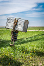 A Rancher's Old Metal Mailbox With A Bridle Wrapped Around It On The Prairies In Rural Saskatchewan, Canada