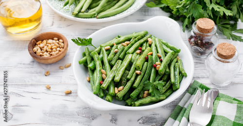 Photo  Sauteed green beans with pine nuts in a baking dish, healthy side dish