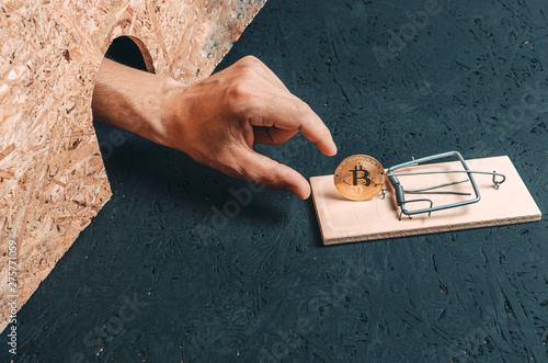 Valokuva  Man hand reaches for the coin bitcoin which is in a mousetrap