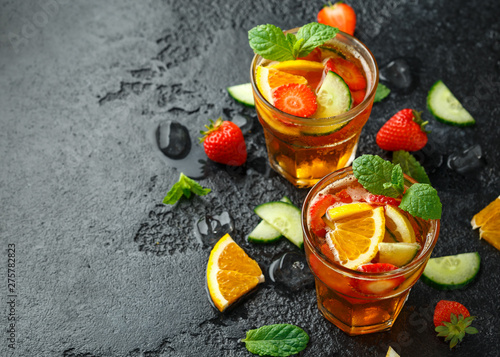 Canvas Prints Countryside Refreshing Pimms Cocktail with Fruit and vegetables on rustic black table