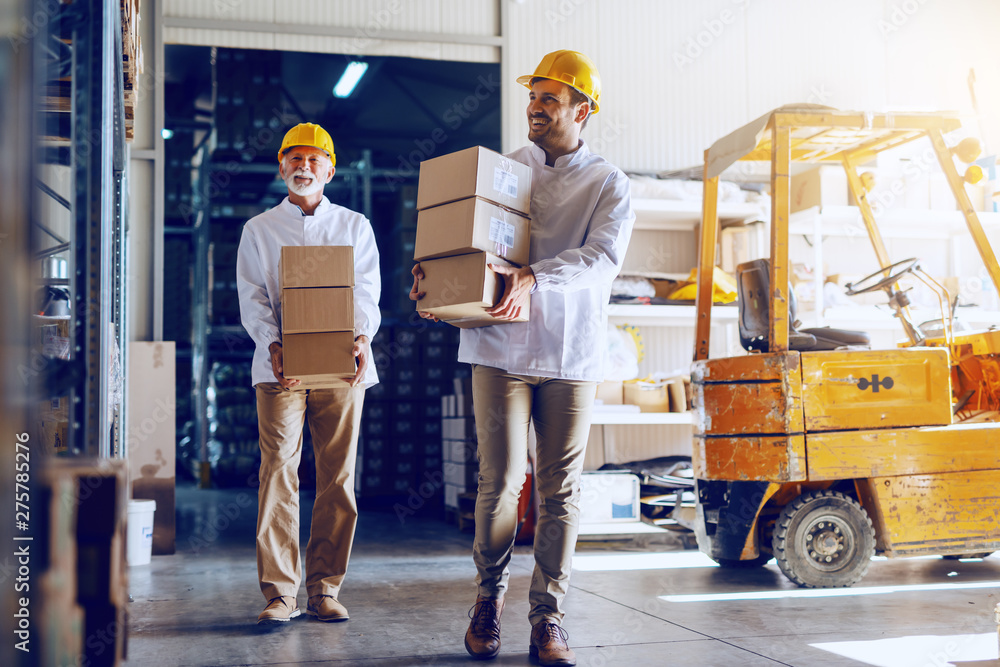 Fototapety, obrazy: Two blue collar workers in white uniforms and with yellow helmets on heads relocating heavy boxes in warehouse.