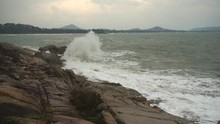 Large Storm Waves Crashing On Rocks In Slow Motion. Foamy Waves Hit The Volcanic Stones Of The Andaman Sea Shore At Stormy Cloudy Weather. Tropical Island Of Koh Samui, Thailand.