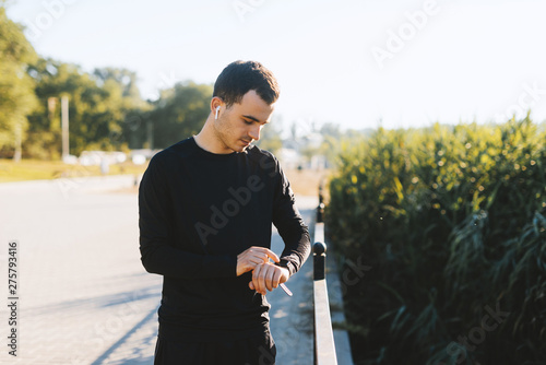 Valokuvatapetti Young man checking his heart rate on his smart watch outdoors in the park after running