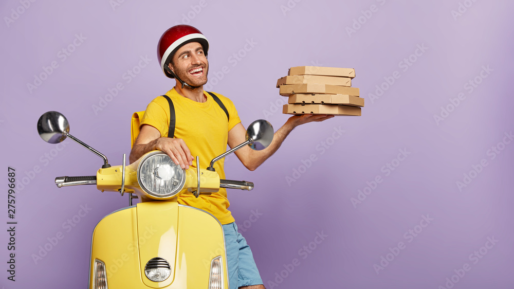Fototapety, obrazy: Delivery service man holds pile of boxes with tasty pizza, reaches destination fast on motorcycle, wears protective helmet, has friendly outlook, brings order for customer. Food transporting concept