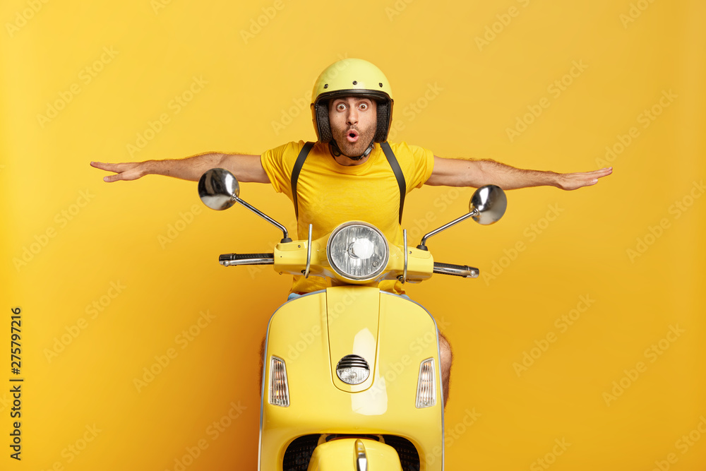 Fototapety, obrazy: Shocked male motorcyclist travels on motorbike, has adventure trip and feels extreme, keeps hands away from handlebars, spreads sideways, likes active rest during summer, drives on high speed.