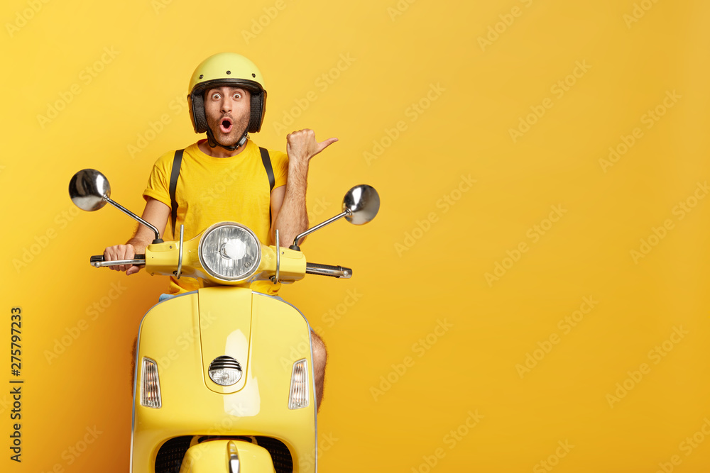Fototapety, obrazy: Impressed driver covers distance on yellow motorbike, wears helmet, indicates with great wonder aside, stops on road, demonstrates blank space for your advertising content, tries new vehicle.