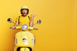 canvas print picture - Impressed driver covers distance on yellow motorbike, wears helmet, indicates with great wonder aside, stops on road, demonstrates blank space for your advertising content, tries new vehicle.