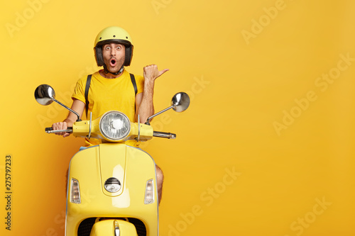 Obraz Impressed driver covers distance on yellow motorbike, wears helmet, indicates with great wonder aside, stops on road, demonstrates blank space for your advertising content, tries new vehicle. - fototapety do salonu