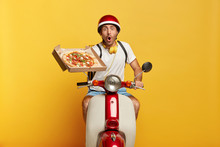 Stupefied Male Expert Driver Holds Pizza Box, Delivers Order To Public, Being On Way To Customer, Shocked Be Late, Poses On Motorcycle In Headgear, Isolated On Yellow Background. Good Service