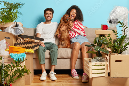 Poster Individuel Relocation, renovation and removal concept. Happy diverse couple sit on sofa with favourite dog, have break on moving day, busy unpacking, have mess in new flat, many packages, remove to own house