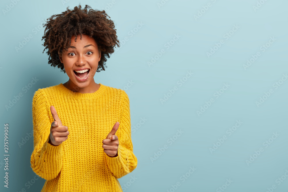 Fototapety, obrazy: Outgoing carefree woman makes finger pistols, points directly at camera with positive expression, says I choose you, wears casual outfit, stands over blue wall with blank space area. You are my type