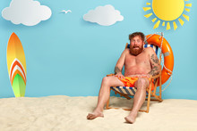 Frightened Bearded Redhead Man Gets Sunburned At Comfortable Beach Chair, Has , Needs Protective Lotion, Surfboard, Lifebuoy And Sea In Background. Summer Time, Holidays And Sunbathing Concept
