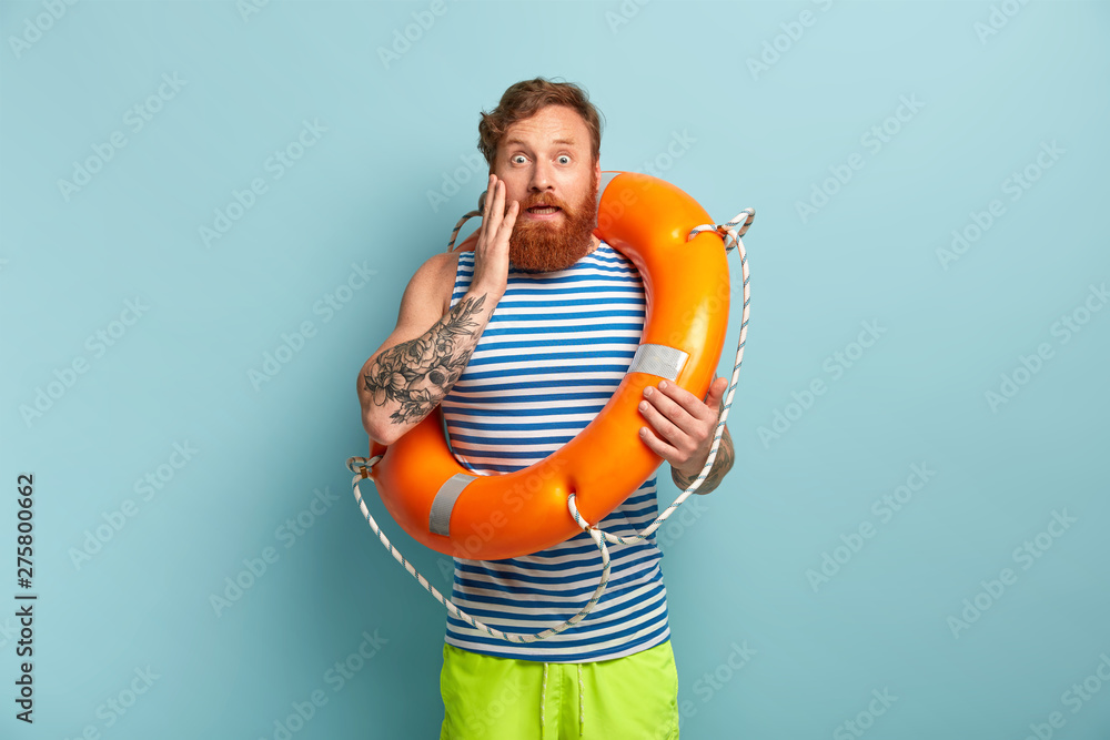 Fototapety, obrazy: Beach safeguard man in sailor vest and green shorts, works at sea resort, has stupefied facial expression, touches cheek, stands inside of orange lifebuoy. Swimmer under supervision of instructor