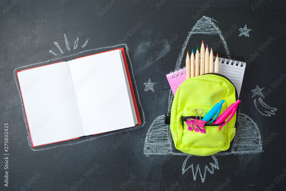 Fototapety, obrazy: Back to school concept with small bag backpack, school supplies and rocket sketch over chalkboad background. Top view from above