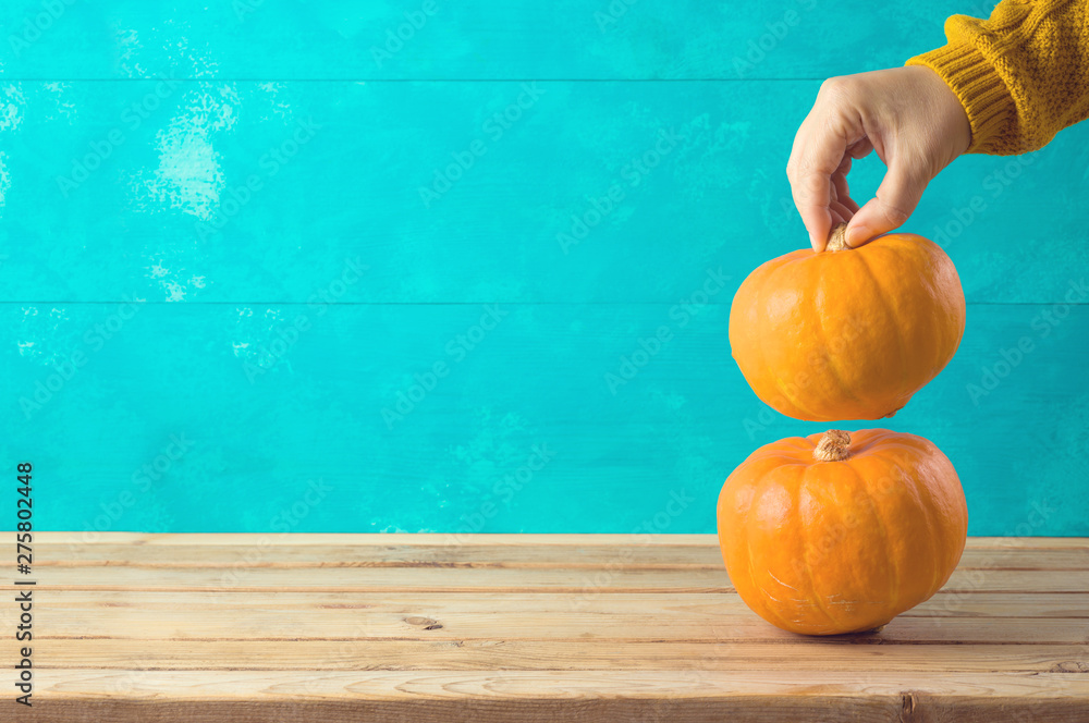 Fototapety, obrazy: Autumn background with pumpkin on wooden table and woman hand.