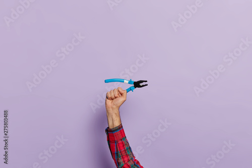 Pinturas sobre lienzo  Mans hand holds pliers with blue plastic handles for construction and repair, isolated over purple background