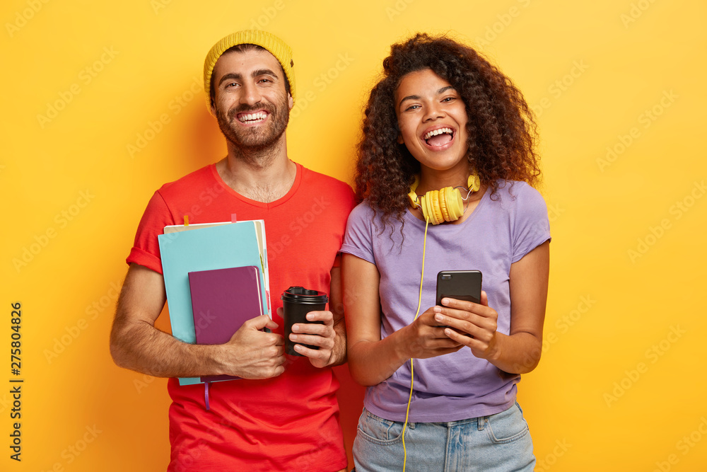 Fototapety, obrazy: Teen students have happy expressions, spend free time together, prepare for exams, hold textbooks, takeaway coffee, mobile phone, dressed in casual apparel, discuss project, isolated on yellow wall