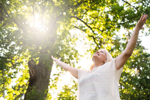 Valokuva  Senior scandinavian woman by the tree holding hands up. Back view