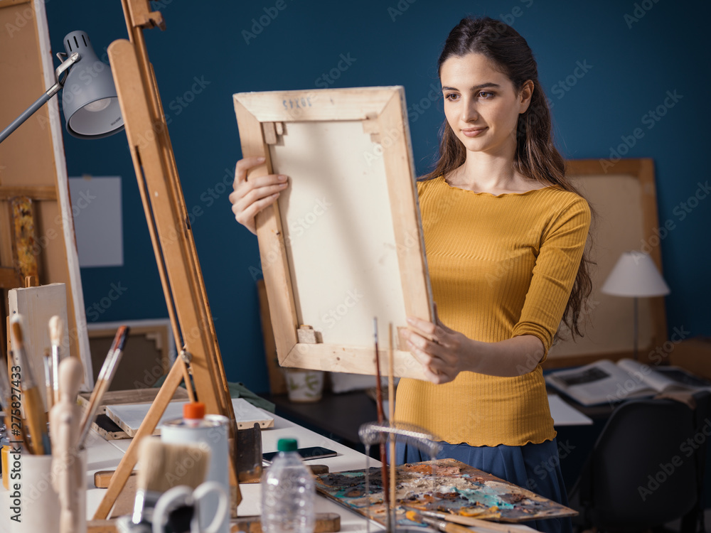 Fototapety, obrazy: Young artist putting a canvas on the easel