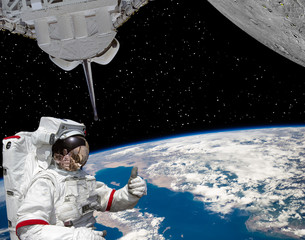 Astronaut gives thumbs-up, earth and planet with craters like moon. The elements of this image furnished by NASA.